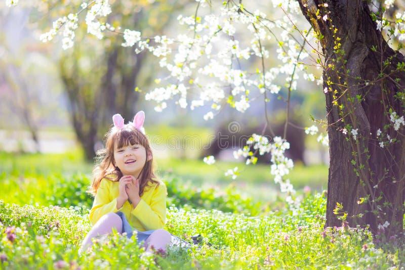 有卷发佩带的兔宝宝耳朵和夏天礼服的逗人喜爱的女孩获得乐趣在放松复活节彩蛋的狩猎期间在庭 免版税图库摄影