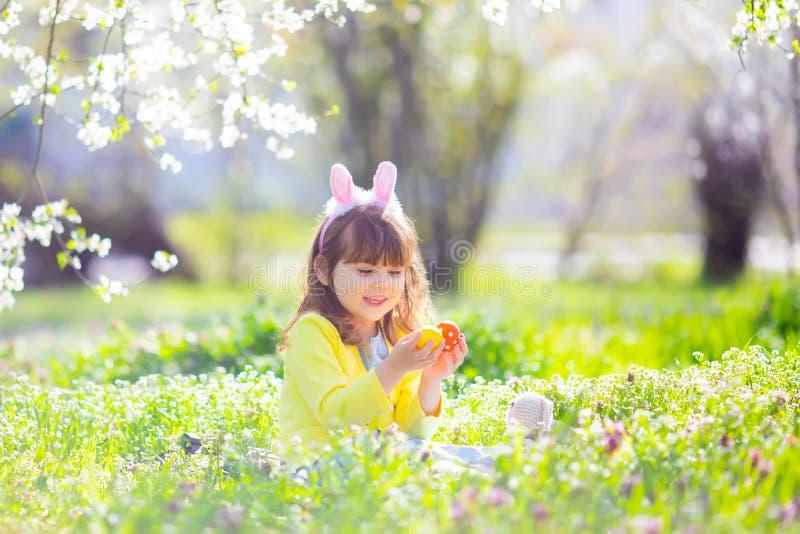 有卷发佩带的兔宝宝耳朵和夏天礼服的逗人喜爱的女孩获得乐趣在放松复活节彩蛋的狩猎期间在庭 库存图片