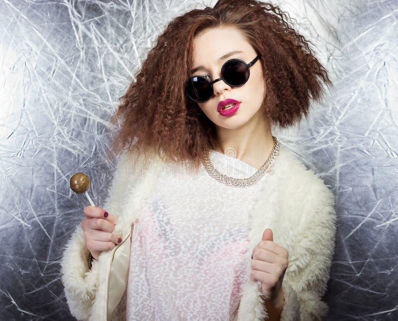 有卷发和明亮的嘴唇的美丽的女孩在圆的太阳镜的一件白色外套用一个糖果在他的手上,演播室射击 库存照片