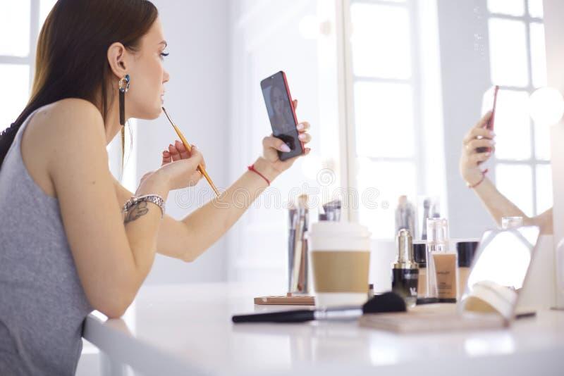 有卷发和构成的女性年轻美女 美女由电话做自画象  免版税图库摄影
