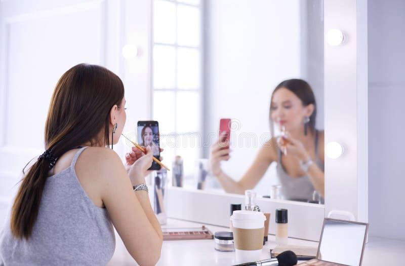 有卷发和构成的女性年轻美女 美女由电话做自画象  图库摄影