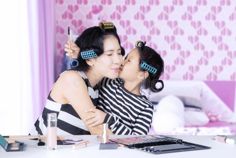 有卷发夹亲吻母亲的逗人喜爱的女儿 库存图片