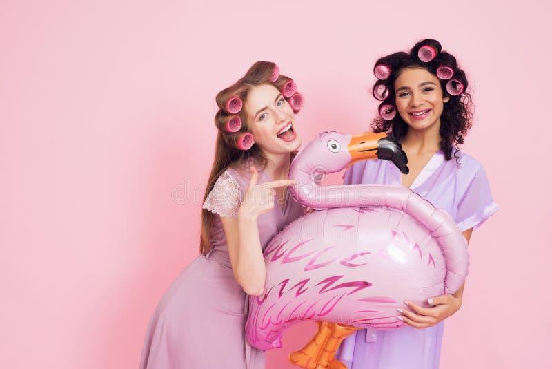 有卷发夹和火鸟baloon的两个女孩 他们庆祝妇女` s天3月8日 库存图片