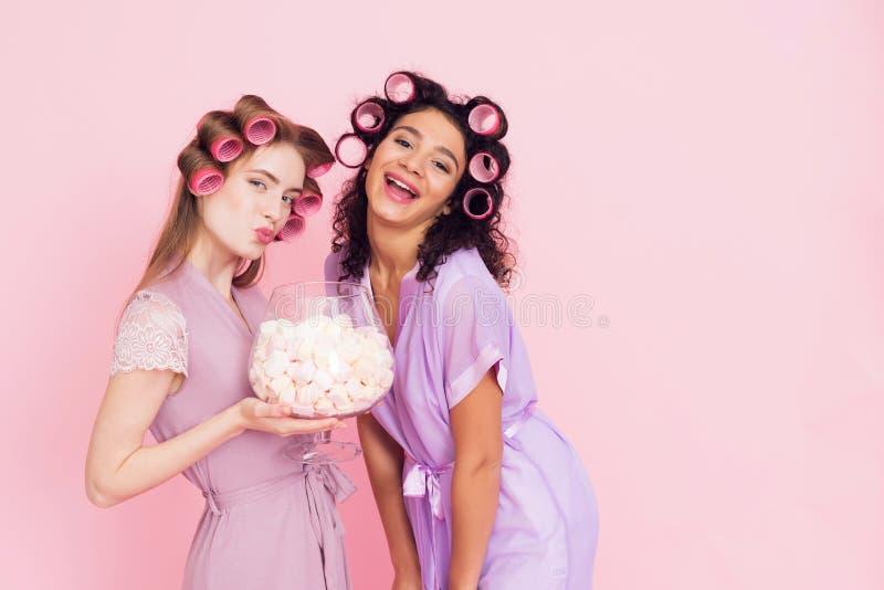 有卷发夹的两个女孩吃marshmellows的 他们庆祝妇女` s天3月8日 免版税库存照片