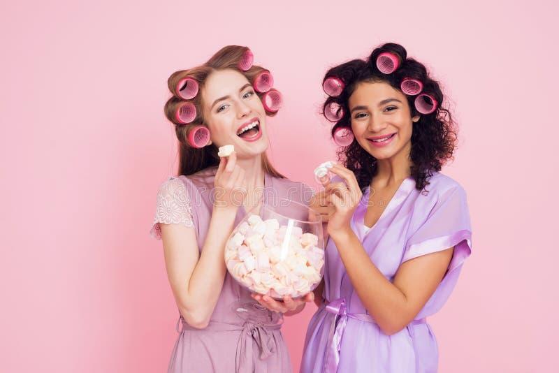 有卷发夹的两个女孩吃marshmellows的 他们庆祝妇女` s天3月8日 库存图片