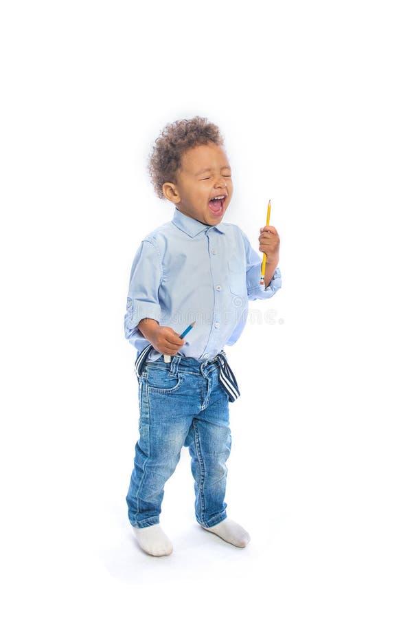 有卷发的一个小深色皮肤的男孩在牛仔裤和一件淡色的衬衣在拿着一支铅笔与的半轮站立 库存图片
