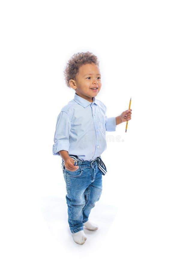有卷发的一个小深色皮肤的男孩在牛仔裤和一件淡色的衬衣在拿着铅笔的半轮站立  免版税库存照片
