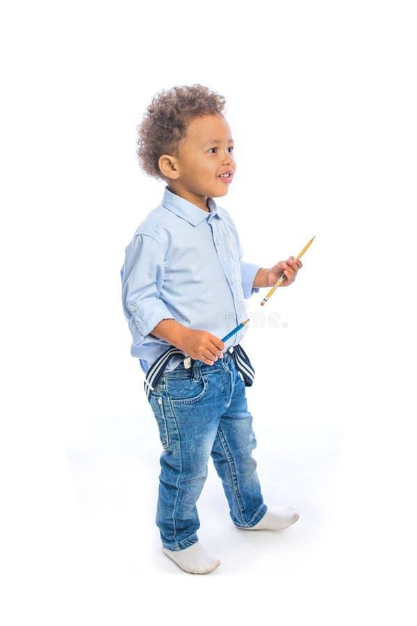 有卷发的一个小深色皮肤的男孩在牛仔裤和一件轻的衬衣在外形站立微笑和进站铅笔的 库存照片