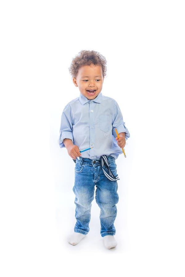 有卷发的一个小深色皮肤的男孩在牛仔裤和一件轻的衬衣在外形站立微笑和进站铅笔的 免版税库存图片