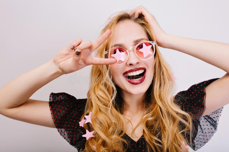 有卷发的享受时间的俏丽的金发碧眼的女人特写镜头画象在党,庆祝,显示和平,微笑对照相机 免版税图库摄影