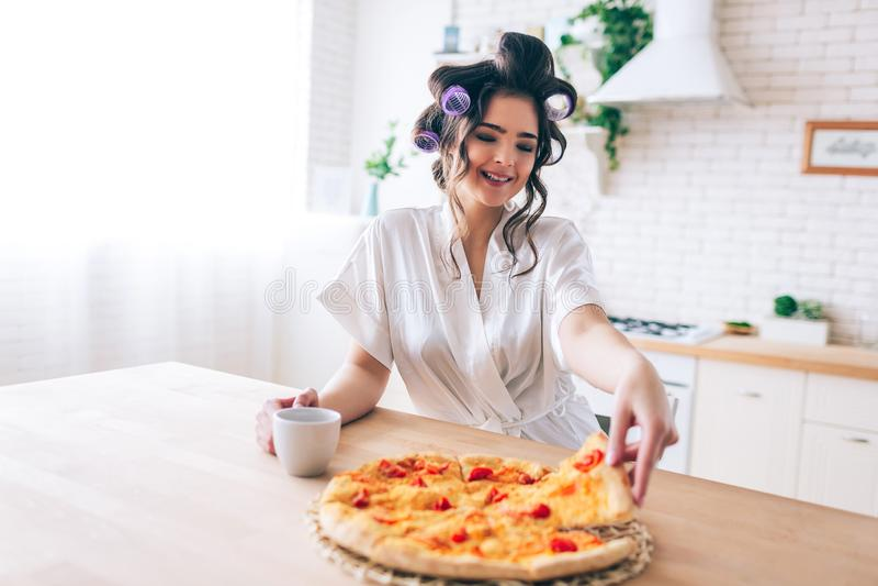 有卷发的人的快乐的好愉快的妇女在采取比萨的pice头发inkitchen 早晨白天 无无忧无虑的人 图库摄影