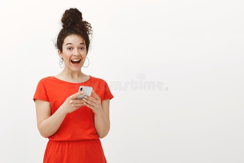 有卷发的在红色礼服,拿着智能手机和大声笑从喜悦的激动的惊奇的愉快的女孩画象 免版税库存图片