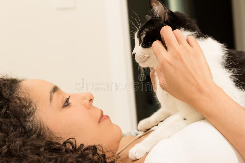 有卷发的女孩在床上的拿着她可爱的家养的黑白猫 爱的概念对动物,宠物的, 免版税库存照片