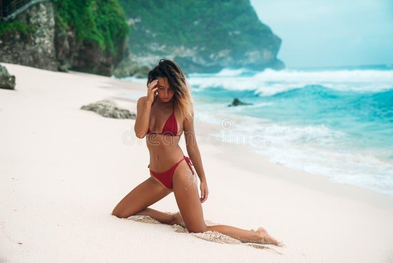 有卷发的女孩浅黑肤色的男人在海滩的红色比基尼泳装与在海洋附近的白色沙子在度假 一个美好的模型 免版税库存照片