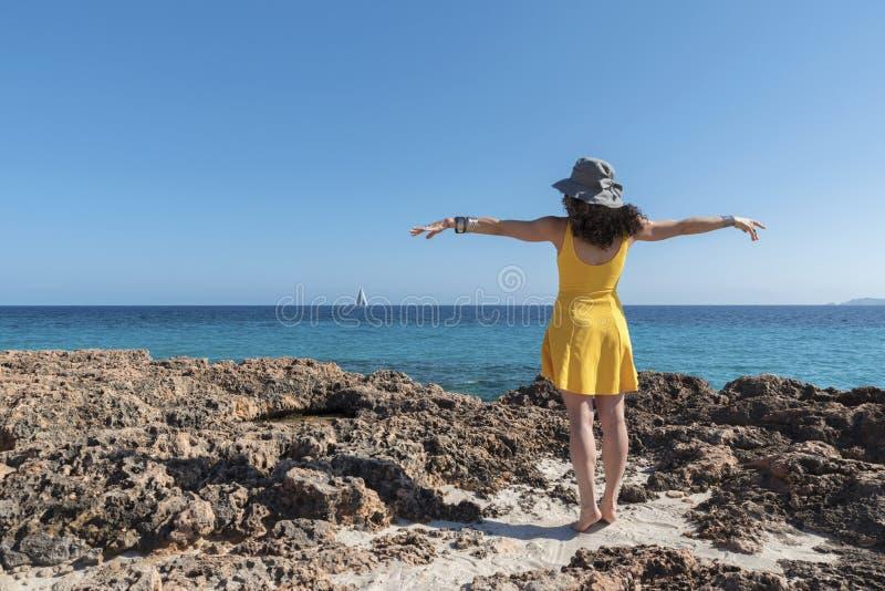 有卷发的妇女在岩石海岸 免版税图库摄影