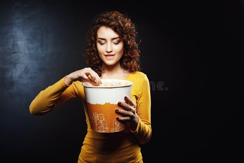 有卷发的妇女采取一些玉米花咬住她的underlip的 免版税库存照片