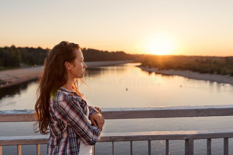 有卷发的少年女孩在生活方式在看日出的桥梁的栏杆附近给身分穿衣 免版税库存图片