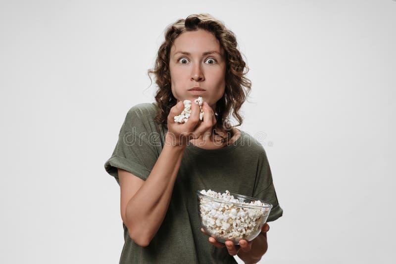 有卷发的年轻女人吃玉米花的,观看电影或电视剧 免版税图库摄影