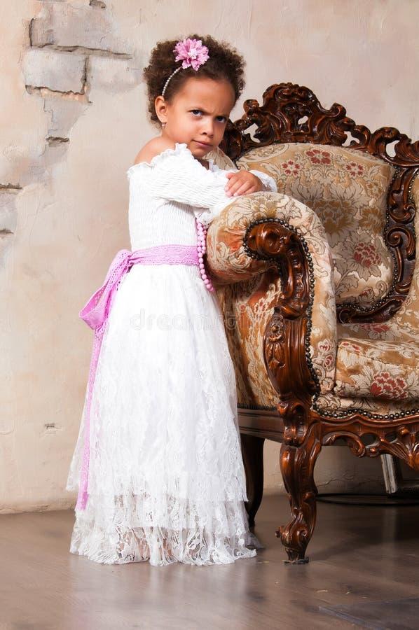 有卷发的微笑的非洲女孩在一根白色鞋带在葡萄酒椅子穿戴 库存照片
