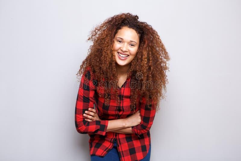有卷发的愉快的少妇微笑反对灰色背景的 免版税图库摄影