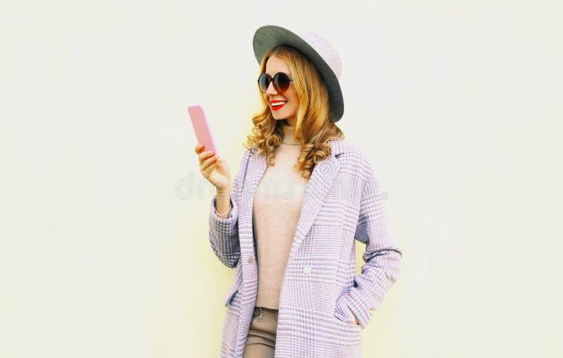 有卷发的愉快的微笑的年轻女人藏品电话在圆的帽子,在背景的桃红色外套夹克 库存图片