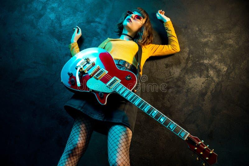 有卷发的时尚年轻行家妇女有在霓虹灯的红色吉他的 岩石音乐家弹电子吉他 图库摄影