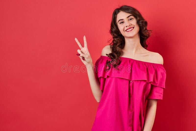 有卷发的深色的女孩在一件桃红色礼服 库存照片