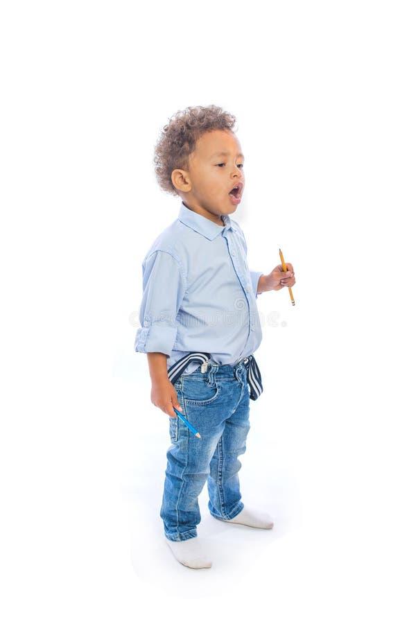 有卷发的男孩在牛仔裤和一件淡色的衬衣在的半轮在两只手中站立拿着铅笔和 免版税图库摄影