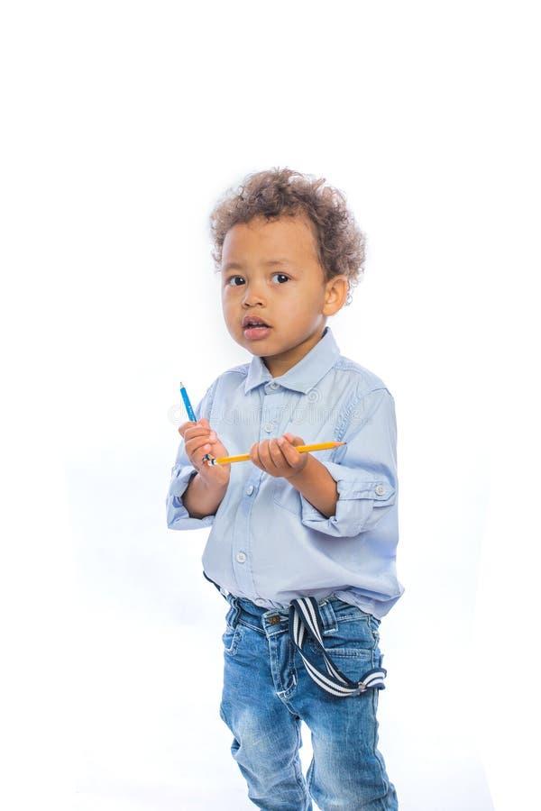 有卷发的男孩在牛仔裤和一件淡色的衬衣在的半轮在两只手中站立拿着铅笔和 免版税库存图片