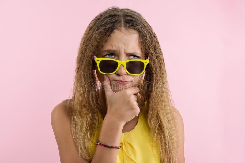有卷发的皱眉十几岁的女孩的金发碧眼的女人,皱眉她的眼眉,当看与安详和周道的神色时 免版税库存图片
