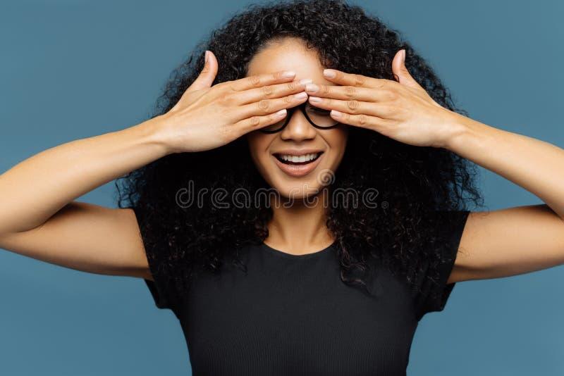 有卷发的秘密妇女,盖眼睛,佩带眼镜,等待惊奇,穿戴在黑偶然T恤杉,摆在反对 库存照片