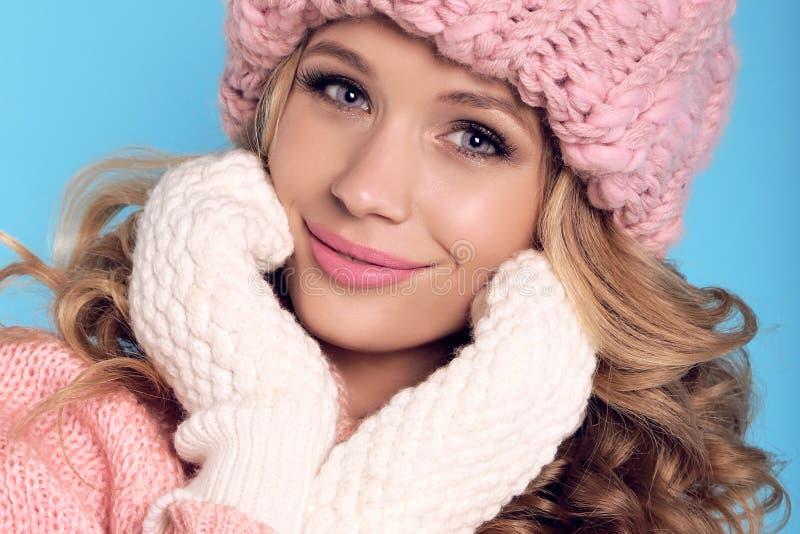 有卷发的美丽的女孩在温暖的舒适冬天穿衣 免版税库存照片