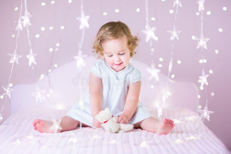 有卷发的美丽的小孩女孩在圣诞灯之间 图库摄影