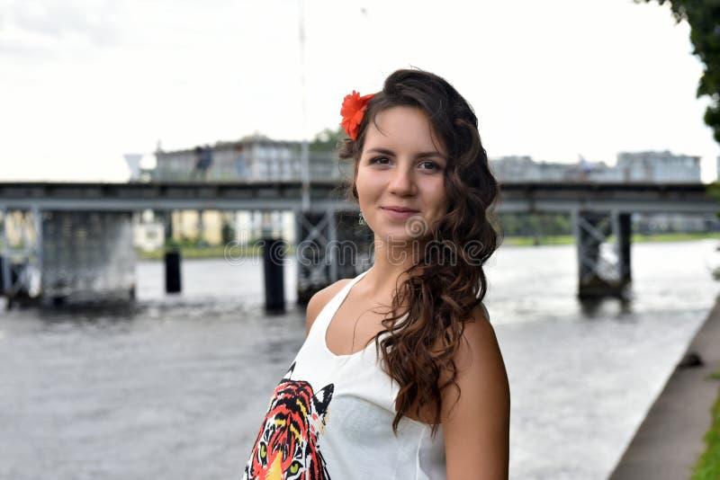 有卷发的美丽的深色的女孩在桥梁的背景 免版税库存照片