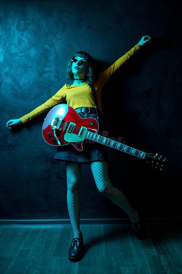 有卷发的肉欲的年轻行家妇女有在霓虹灯的红色吉他的 岩石音乐家弹电子吉他 免版税图库摄影