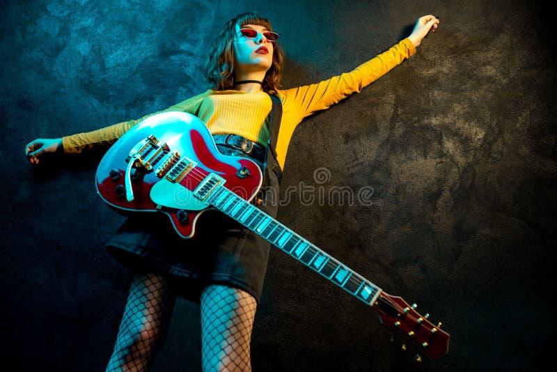 有卷发的迷人的行家妇女有在霓虹灯的红色吉他的 岩石音乐家弹电子吉他 90s 免版税库存照片
