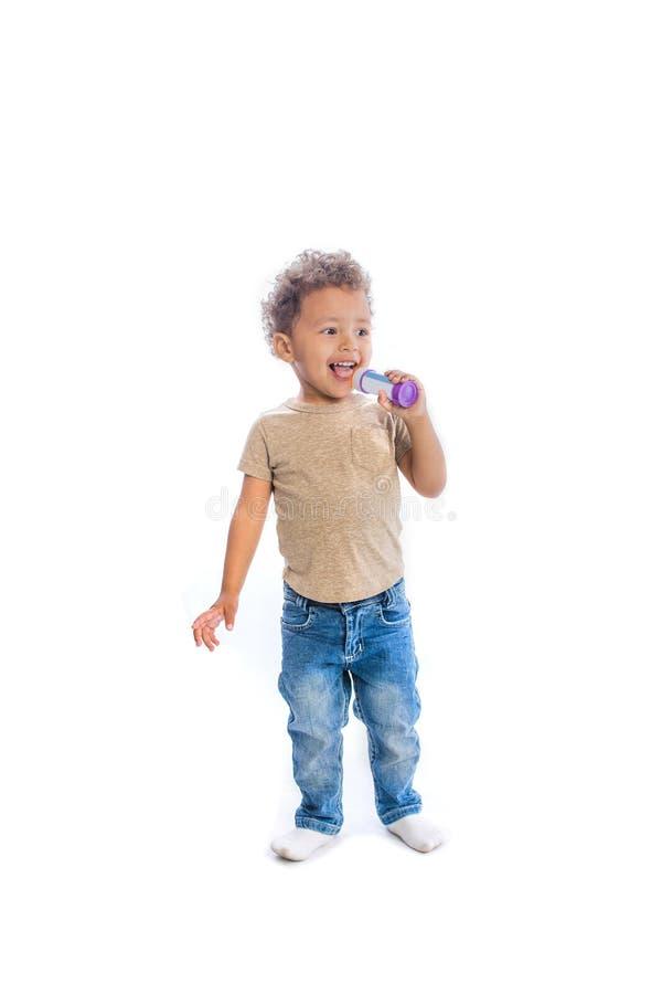 有卷发神色的一个小深色皮肤的婴孩对旁边微笑唱某事仿效话筒的使用箱子 库存照片