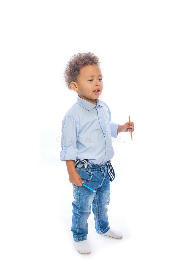 有卷发神色的小深色皮肤的婴孩对微笑的边,被隔绝的背景 库存照片