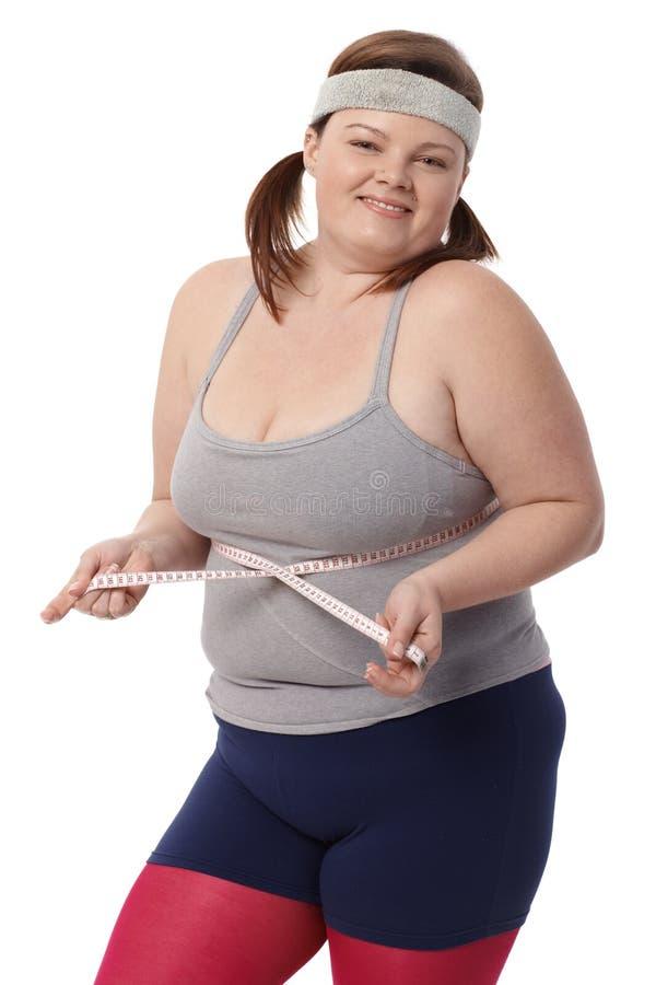 有卷尺的愉快的肥胖妇女 免版税库存图片