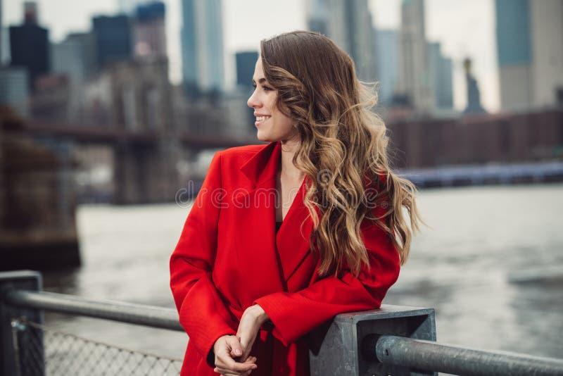 有卷曲发型的典雅的女实业家微笑和看对边的 免版税图库摄影