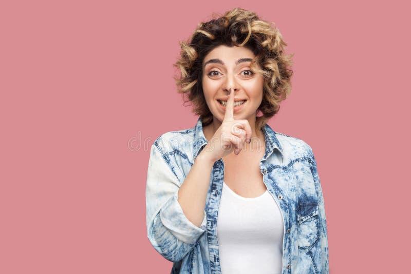 有卷曲发型的在偶然蓝色衬衣身分,告诉秘密和看与手指的忧虑年轻女人画象照相机 库存照片