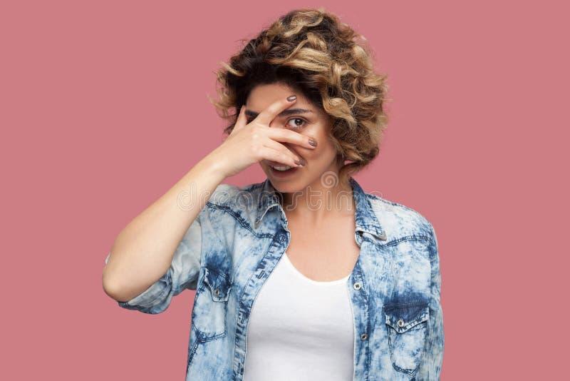 有卷曲发型的在偶然蓝色衬衣身分,盖她的眼睛和看通过手指的滑稽的年轻女人画象 免版税库存照片
