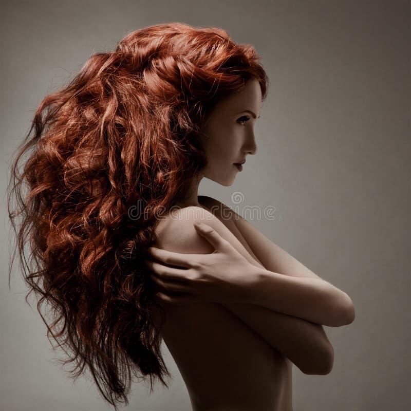 有卷曲发型的美丽的妇女 免版税库存照片