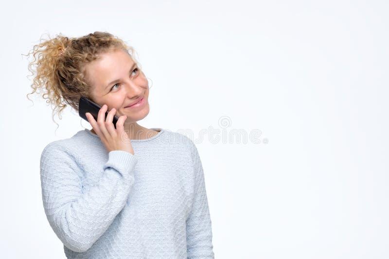 有卷曲发型的逗人喜爱的快乐的妇女谈话在手机 库存照片