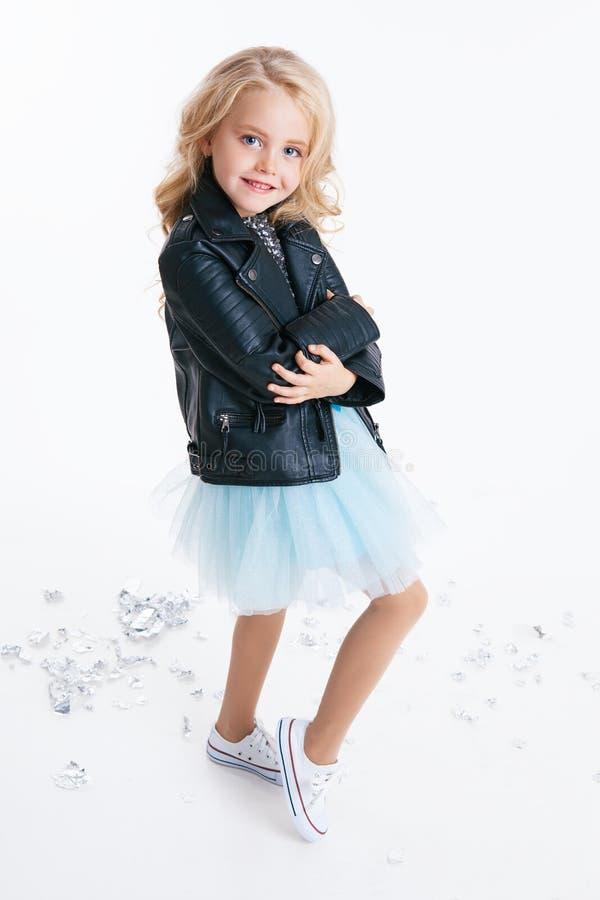 有卷曲白肤金发的发型选址的美丽的小女孩在礼服的节日晚会有衣服饰物之小金属片和黑夹克的 图库摄影