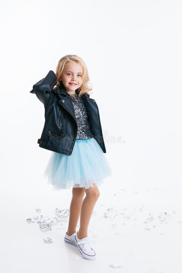 有卷曲白肤金发的发型选址的美丽的小女孩在礼服的节日晚会有衣服饰物之小金属片和黑夹克的 免版税库存图片