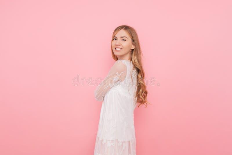 有卷曲的头发的愉快的女孩在桃红色背景的一件白色礼服 库存图片