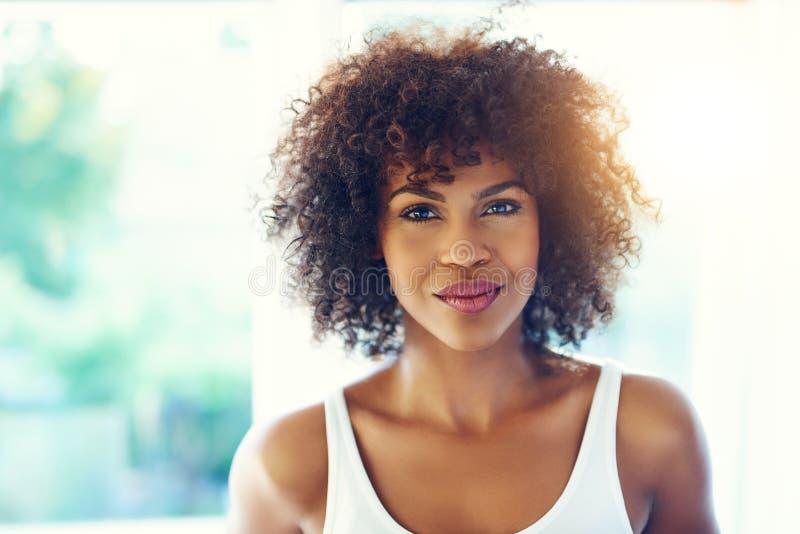 有卷曲的蓬松卷发头发的美丽的年轻黑人妇女 库存照片