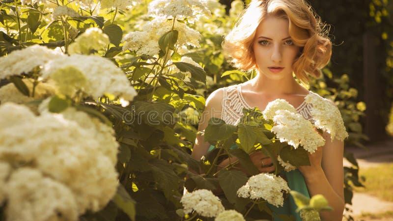 有卷曲短的突然移动发型的美丽的白肤金发的妇女,精美 免版税库存照片