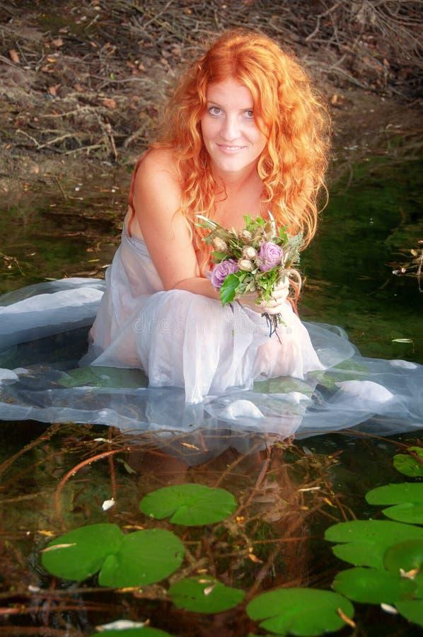 有卷曲红色头发的年轻性感的妇女坐快乐,与白色礼服愉快在水中在湖 免版税库存图片